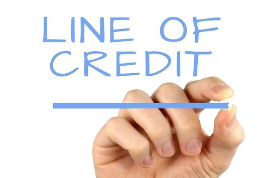A hand drawing a line of credit to remind you to check with your bank if you can afford a machinery loan