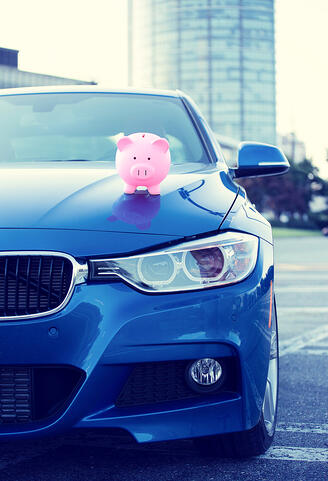Piggy bank on top of expensive used car for sale that offers monthly repayments