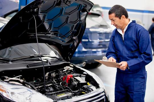 Mechanic inspecting a used car before owner can decide to purchase used vehicle.